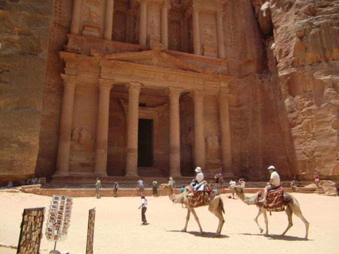 アル・ハズネ遺跡正面の景色ととラクダに乗る旅人