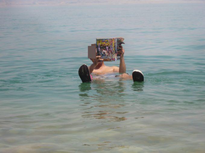 死海で浮きながらジャンプを読む作者