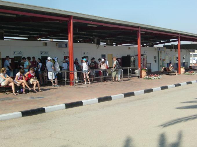 入国ゲートでバスを待つ人々